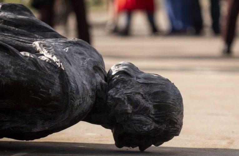 Estatuas frente a manifestantes